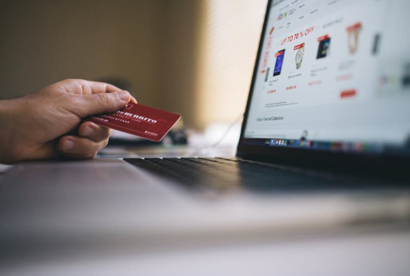 Man holding credit card to make online purchase