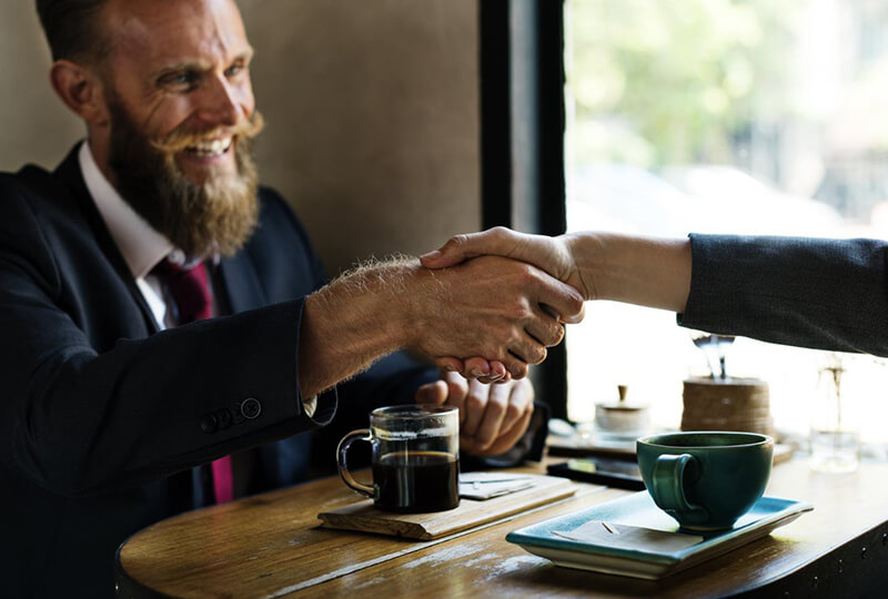 Man in suit shaking hands with colleague at coffee shop